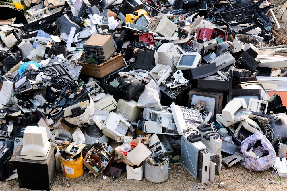 Large pile of electronic waste at outdoor dump